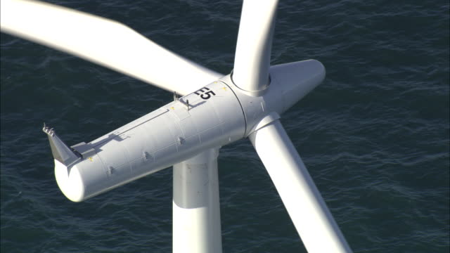 Aerial shot of a wind turbine spinning off the coast of Denmark.