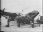 Aerial shot of abandoned Nazi airplanes in Tunisian desert / Allied soldiers repairing abandoned German Stuka plane on desert airfield / soldier...