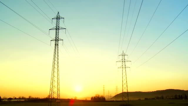 Aerial Shot Of Electricity Pylons At Sunset