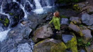 Aerial Shot of Female Hiker Looking Up at Waterfall