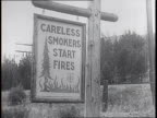 Aerial shot of forest fires / 'Careless Smokers Start Fires' sign / workers load supplies into an airplane / parachute firemen in asbestos suits...