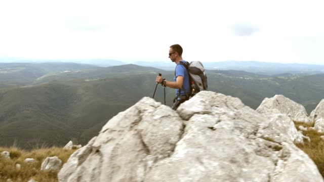 Aerial shot of man hiking along the mountain edge