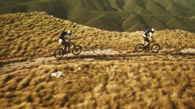 Aerial shot of mountain bikers riding on plateau top