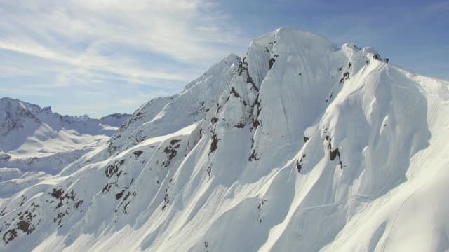 Aerial shot of skiers skiing from the top of a mountain.