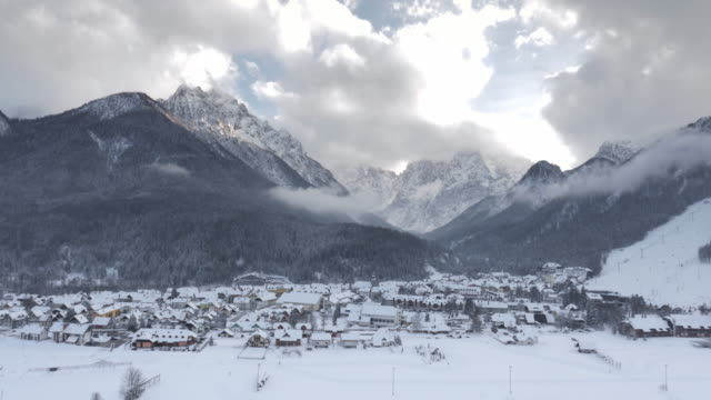 Aerial shot of snowy alpine valley below the mountain tops