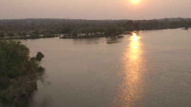 Aerial shot of the sun shining on calm water as it approaches the Victoria Falls at dusk, Zambia.
