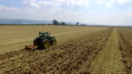Aerial shot of tractor ploughing dry Field in the Hula valley