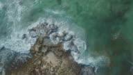 Aerial shot of waves on rocky coastline