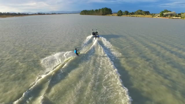 Aerial shot of young man wake boarding behind a motorboat in a lake.  - Slow Motion