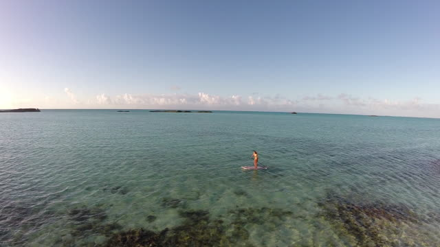 Aerial shot of young woman standup paddleboarding.