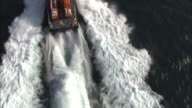 Aerial shot over an RNLI lifeboat as it speeds across the water.