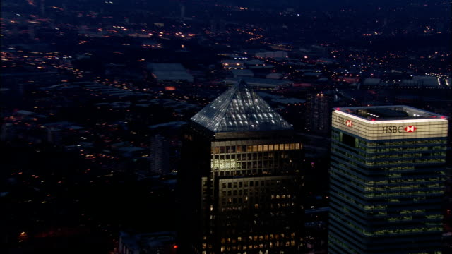 Aerial shot pulling away from tops of skyscrapers in Canary Wharf at dusk / London