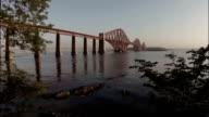 Aerial shot revealing the Forth Rail Bridge outside Edinburgh during sunrise on a calm summer morning