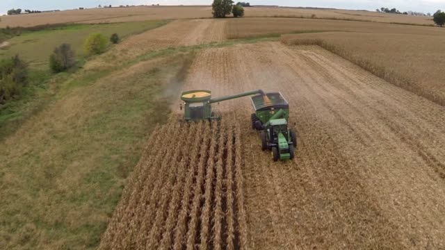 Aerial shots focus on a John Deere tractor and a Combine Harvester as they collect corn seed from a field in Tskilwa Illinois