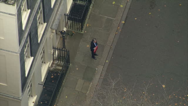 Aerial shots of Chancellor Philip Hammond walking out of Number 11 Downing Street and posing with the red Budget box before getting into a waiting...