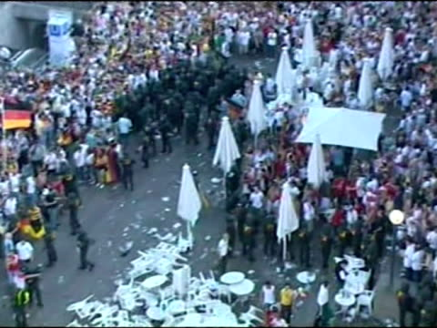 Aerial shots of football fans outside stadium with pile of garden chairs and tables stacked in middle looking like they've been thrown Riot police...