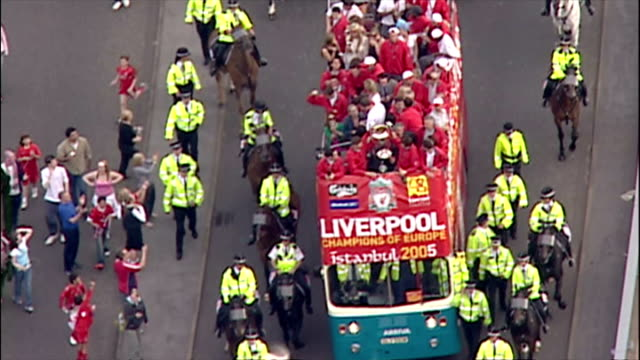 Aerial shots of Steven Gerrard and Jamie Carragher lifting and holding Champions League European Cup trophy on open top bus parade surrounded by...