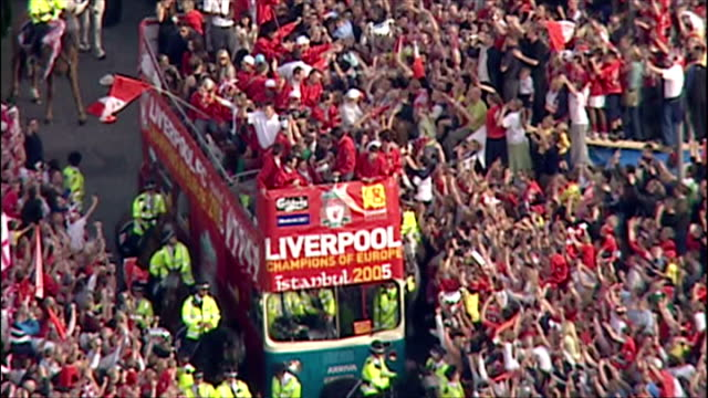 Aerial shots of thousands of Liverpool FC supporters fans surrounding open top bus as Liverpool players show off European Cup Champions League trophy...