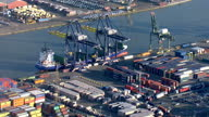 Aerial shots of Tilbury docks container port Samskip logistics company logo on containers Containers lined up at docks and container ship being...