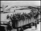 Aerial shots of US military base in Okinawa hundreds of planes are parked on air strips / truck pulling carts filled with soldiers / 'Tokyo Trolley'...