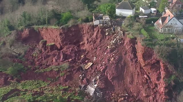 Aerial shots remains of house sit on edge of cliff after storm and heavy rains caused landslide severely damaging house Debris from house is...