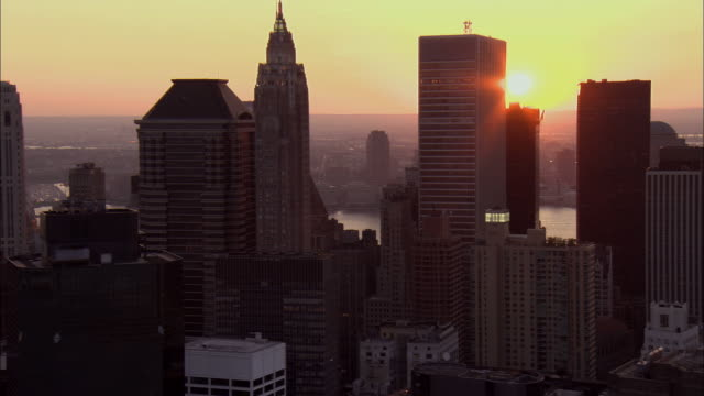 Aerial WS Silhouetted skyscrapers in Lower Manhattan at sunset including Deutsche Bank headquarters at 60 Wall Street, Woolworth Building, Trump Building, and World Financial Center / Manhattan, New York, New York, USA