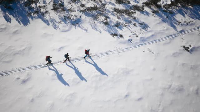 Aerial Ski tourers skiing along a path across the mountain
