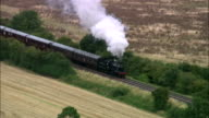 Aerial steam locomotive traveling through countryside on Great Central Railway / England