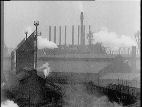 Aerial steel mills / vast steel mills black themselves out with aid of secret chemicals / smoke stacks steel mills and locomotives billow smoke /...