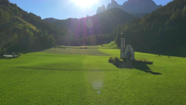 Aerial sun flare view St Johann chapel Dolomites