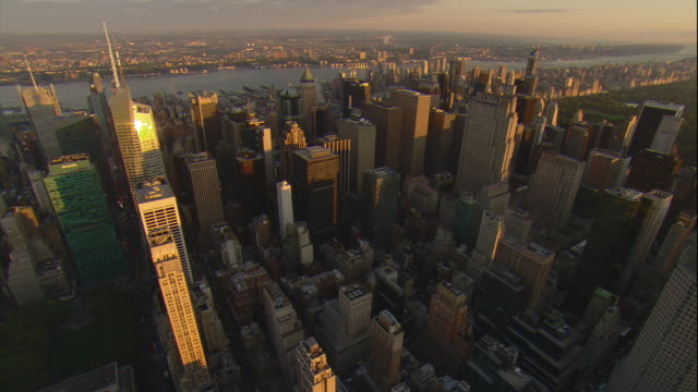 Aerial -Sunrise lights up the tall buildings of mid-town Manhattan while flying toward Central Park.