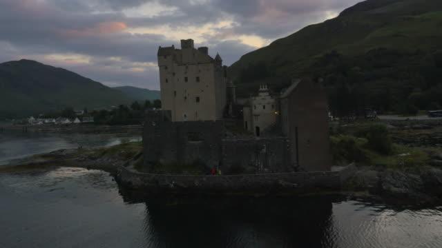 Aerial sunset view Eilean Donan castle tourists Scotland