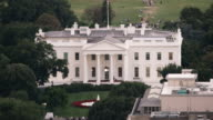 Aerial tight shot of The White House surrounded by trees, DC daytime