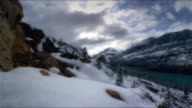 Aerial time lapse over snowy mountainside in Banff National Park with mountains in background/ Alberta, Canada