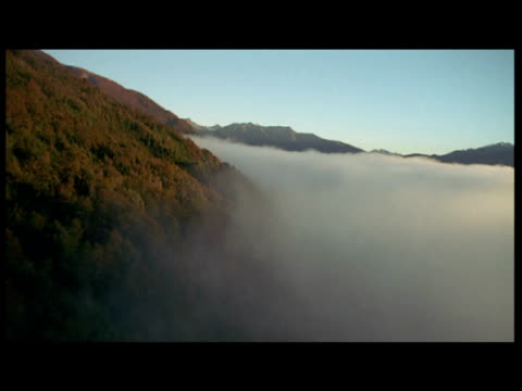 Aerial track along edge of mist smothered valley