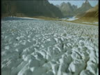 Aerial track down over fissured glacier in mountainous valley