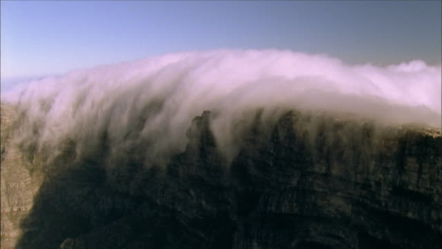 Aerial track left over Table Mountain as clouds boil off of the top Available in HD.
