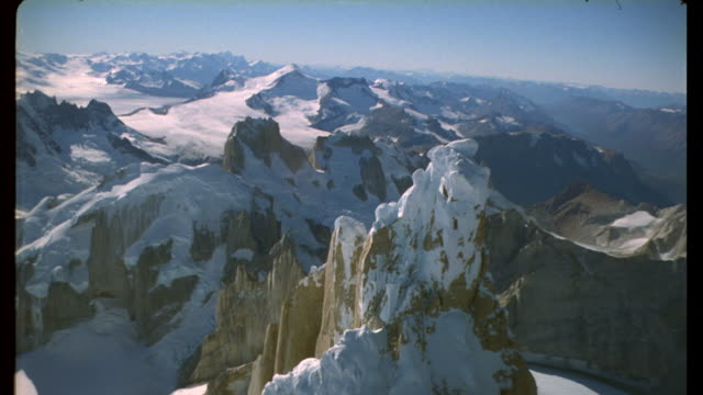 Aerial track towards and over snowy jagged mountain peak Available in HD.