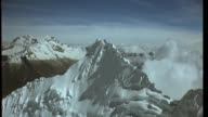 Aerial track towards and over summit of ice capped Andean mountain Available in HD.