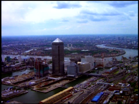 Aerial track towards Canary Wharf Tower with adajecent tower under construction, London; 1990's