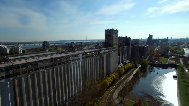 Aerial tracking shot along abandoned factory in Montreal Port