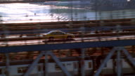 Aerial tracking shot along Manhattan Bridge with taxi and subway crossing towards Manhattan / NYC