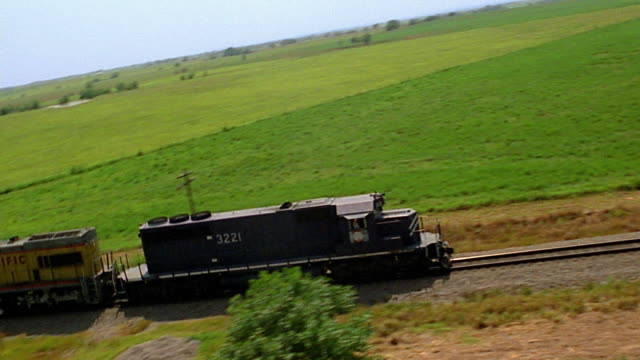 Aerial tracking shot freight train moving past fields