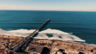 Aerial tracking shot of a beautiful sunrise sparkling off the ocean as the pier is revealed.