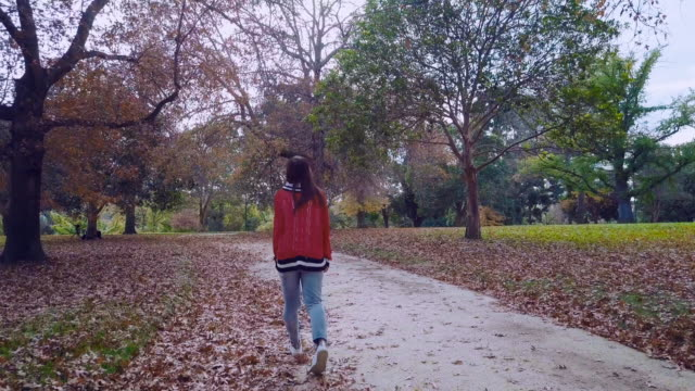 Aerial tracking shot of a young millennial woman walking and kicking autumn leaves