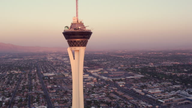 Aerial video flying around Stratosphere Casino, Hotel & Tower, Sunset