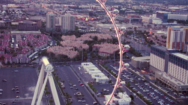 Aerial video flying over Las Vegas looking at Ferris wheel of High Roller, sunset
