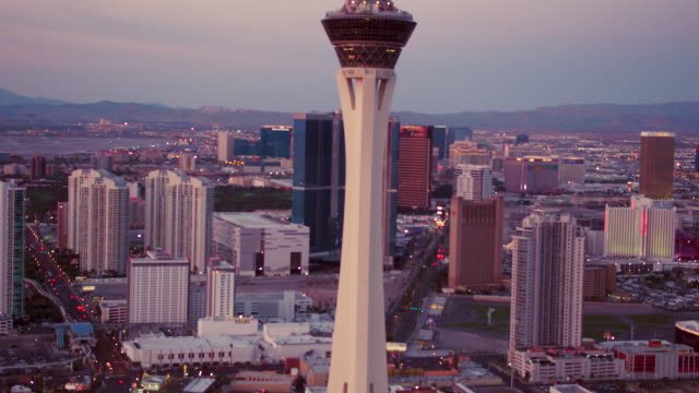 Aerial video flying South towards Stratosphere Casino, Hotel & Tower and Las Vegas Strip, Sunset