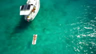 aerial video of a sloop anchored in the Caribbean bay