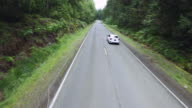 Aerial video of a small car driving on secluded road